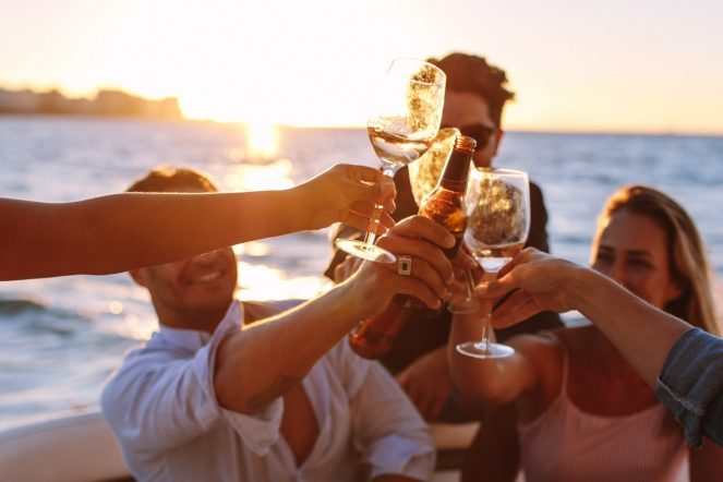 Sunset,Boat,Party,With,Young,People,Toasting,Drinks.,Group,Of